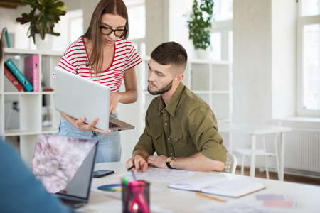 Photo for Young thoughtful man in shirt and woman in striped T-shirt and eyeglasses thoughtfully working together with laptop. Business people spending time at work in modern office - Royalty Free Image
