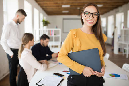 Photo for Young smiling business woman in eyeglasses happily looking in camera holding folder in hands in office with colleagues on background - Royalty Free Image