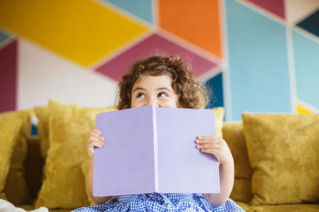 Photo for Pretty little girl with dark curly hair in blue dress happily looking aside covering mouth with book on sofa at home - Royalty Free Image