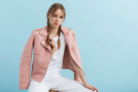 Foto de Young attractive pensive girl with two braids in pink leather jacket and white jeans dreamily looking in camera over blue background - Imagen libre de derechos