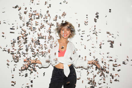 Photo pour Beautiful smiling girl in white shirt happily looking in camera with confetti around over white background - image libre de droit
