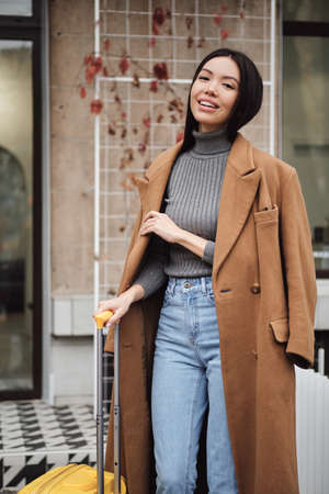 Photo pour Attractive smiling stylish Asian girl in coat happily looking in camera with yellow suitcase on city street - image libre de droit