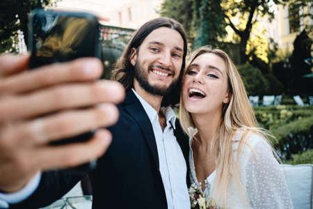 Photo pour Young attractive cheerful groom and bride happily taking selfie together in garden of restaurant - image libre de droit