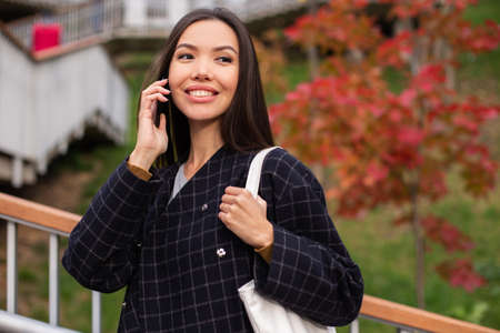 Photo for Young beautiful casual woman in coat joyfully talking on cellphone in autumn park - Royalty Free Image