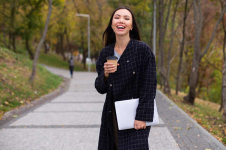 Photo for Young attractive cheerful woman in coat with coffee to go and laptop joyfully walking in autumn park - Royalty Free Image