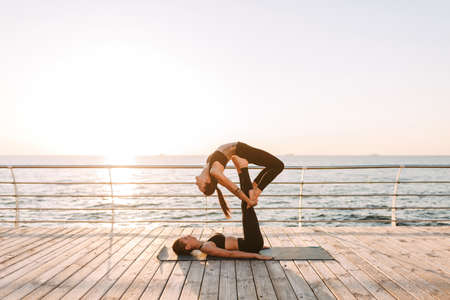 Photo pour Photo of two beautiful ladies in black sporty tops and leggings training yoga poses by the sea. Young women practicing yoga together with beautiful sea view on background - image libre de droit