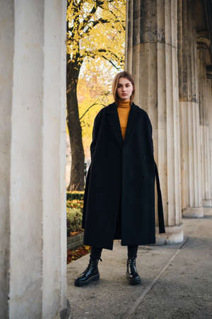 Photo for Beautiful stylish girl in black coat and boots intently looking in camera outdoor - Royalty Free Image