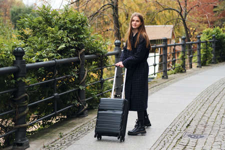 Photo for Attractive stylish girl in coat dreamily walking around street with suitcase - Royalty Free Image