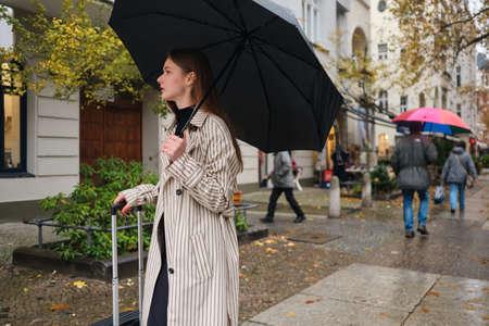 Photo for Beautiful stylish girl walking around rainy city street with umbrella and suitcase - Royalty Free Image