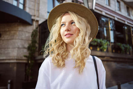 Photo for Portrait of attractive casual blond girl in hat dreamily looking away walking on city street - Royalty Free Image