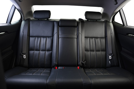 Foto de Back passenger seats in modern luxury car, frontal view, black perforated leather, isolated on white, clipping path included. - Imagen libre de derechos