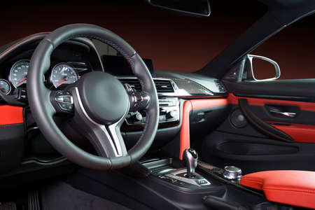 Photo pour Modern luxury car Interior - steering wheel, shift lever and dashboard. Car interior luxury inside. Steering wheel, dashboard, speedometer, display. Red and black leather cockpit - image libre de droit