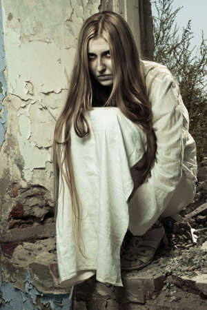 zombie girl sitting in abandoned building