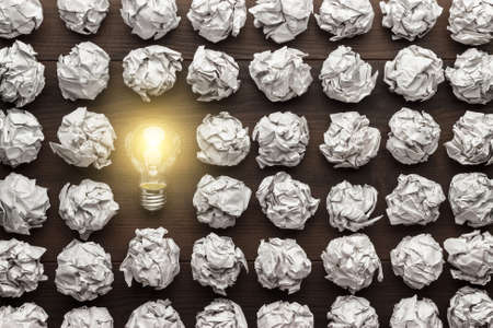 Foto de new idea concept with crumpled office paper and light bulb - Imagen libre de derechos