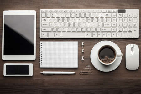 overhead of essential office objects in order on wooden desk