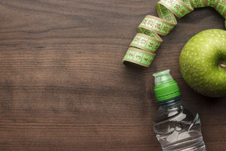 bottle of water, measuring tape and fresh green apple on the wooden table