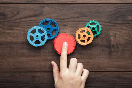 Photo for perfect solution concept. colorful gears and hand on the brown wooden background - Royalty Free Image