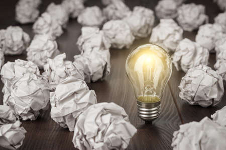 Foto de great concept with crumpled office paper and light bulb standing on the table - Imagen libre de derechos