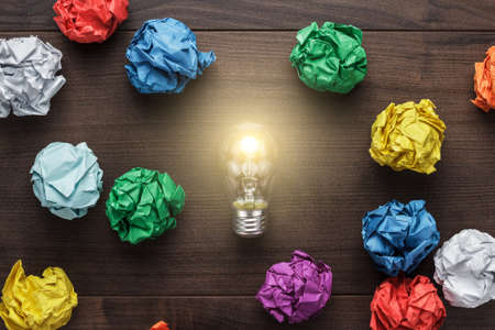 Photo for best idea concept with crumpled colorful paper and light bulb on wooden table - Royalty Free Image