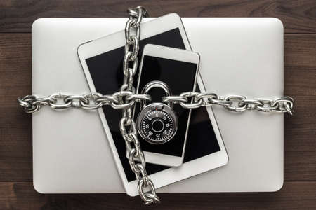 Photo for data security concept: computer, tablet, phone bound by metal chain and closed with combination lock on wooden table - Royalty Free Image