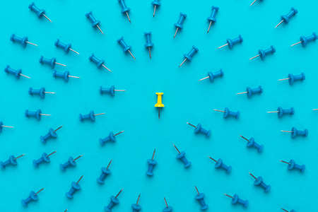 Foto de Yellow push pin in the center of blue push pins with their spike turned to the yellow one as a concept of bullying or discrimination. - Imagen libre de derechos