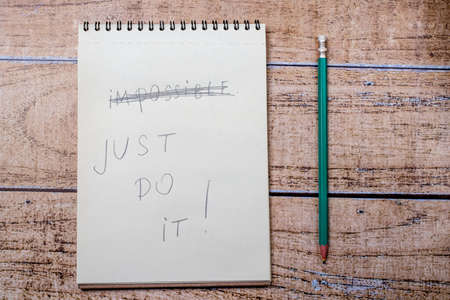 Foto per Notepad and pencil, inscription Just do it. Quote about success and goal achievement in business and life - Immagine Royalty Free