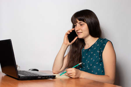 Photo pour A businesswoman in the office is on the phone sitting at a desk with a laptop - image libre de droit
