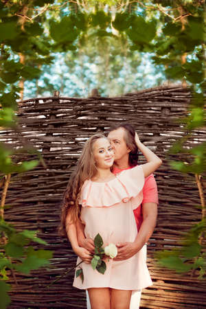 Cute future parents posing in summer nature on the background of the braided wall. Pregnant wife hugging her husband, and the man embracing her belly
