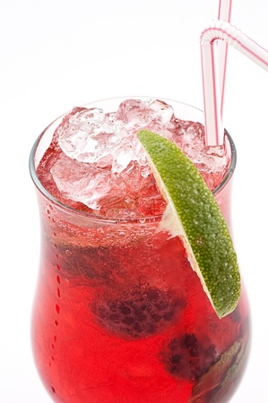 Cocktail with a raspberry and a blackberry with ice slices in a transparent glass close up