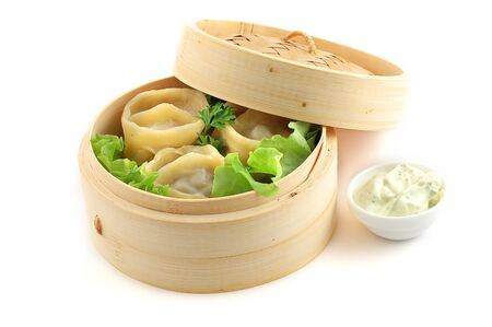 Chinese dumpling in steam basket over white background