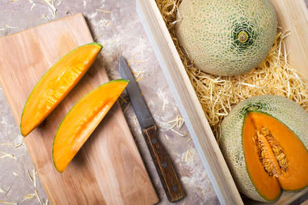 Photo for melons in a wooden box in straw. pieces of melon with a knife on the board. - Royalty Free Image