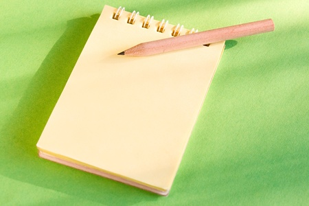 Notepad and pencil on the green background