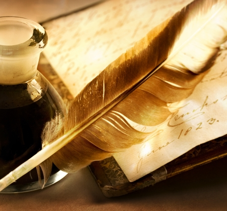 Old book with feather and the inkpot full of ink