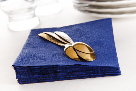 Stack of paper napkins with spoons, plates and glasses