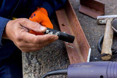 Photo pour The worker uses a rivet hand gun, and inserts a rivet into it. Manual rivet wrench. - image libre de droit