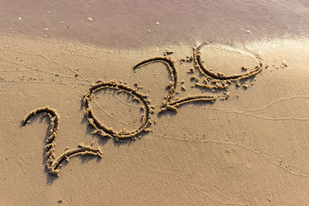 Photo pour The year 2020 is written on the sandy shore. 2020 comes to an end and is washed away by the wave. Summer background. - image libre de droit