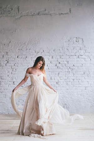 Photo pour Fashion model in a beautiful beige flowing dress. - image libre de droit