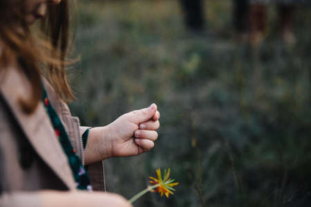 Foto de fair-haired girl in a beige coat touching flower on the dry grass and autumn trees background. - Imagen libre de derechos