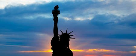 The silhouette of Statue of Liberty under sunrise background