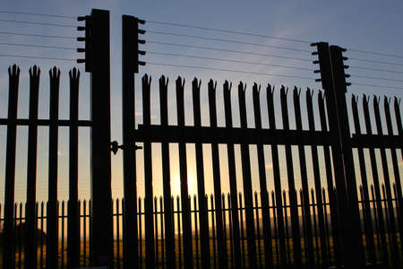 High security steel and razor wire fence, with unreachable sunset landscape behind it