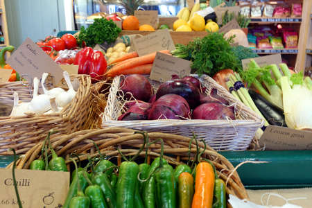 Brightly coloured selection of healthy organic vegetables in wicker baskets, including chilli, garlic, red onion,pepper, tomato and carrot.