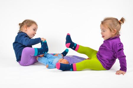 Photo pour Twins playing with doll babies - image libre de droit