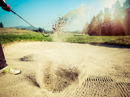 Photo for Golfer hitting out of a sand trap. The golf course is on the sand. Sand making splashes. Sun and sunshine in the background - Royalty Free Image