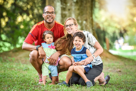Happy interracial family is enjoying a day in the park. Little mulatto baby girl and boy. Successful adoption. Diverse family in nature with sun in the back.