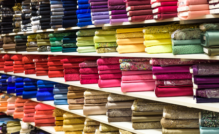 Rolls of fabric and textiles in a factory shop or  store or bazar. Multi different colors and patterns on the market. Industrial fabrics.