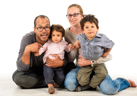 Happy interracial family is celebrating, laughing and having fun with Hispanic African American Father, Caucasian mother and Mulatto children son and daughter.  Isolated on white.の写真素材