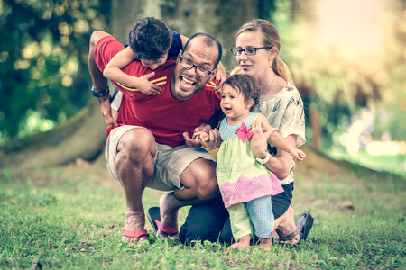 Happy interracial family is active and enjoying a day in the park. Little mulatto baby girl and boy. Successful adoption. Diverse family in nature with sun in the back. Healthy lifestyle.