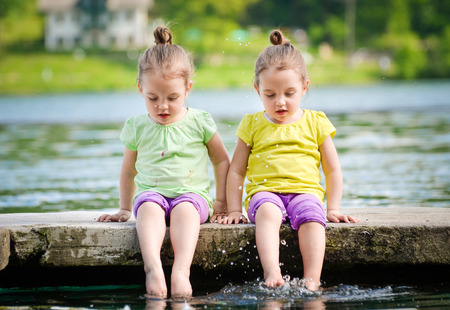 Foto de Twin girls are exercising on a lake shore, sprinkling water. - Imagen libre de derechos