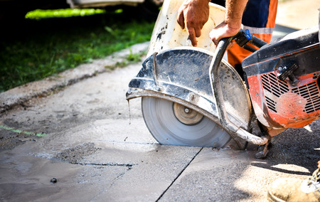 Foto de Construction worker cutting Asphalt paving stabs for sidewalk using a cut-off saw. Profile on the blade of an asphalt or concrete cutter with workers shoes and protective gear. - Imagen libre de derechos