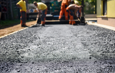 Foto de Team of Workers making and constructing asphalt road construction with finisher. The top layer of asphalt road on a private residence house driveway - Imagen libre de derechos
